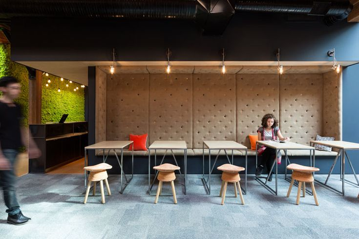 For Slack's Vancouver Office, Leckie Studio Updates Industrial Warehouse for Modern Work. In a break-out area, custom upholstery was finished with wooden buttons.