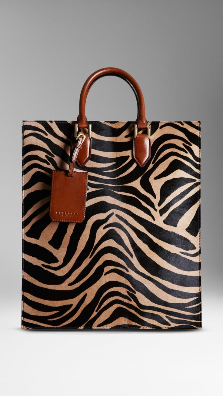 Burberry - Striped Animal Print Tote Bag $2,295.00 Item 38949521 CAMEL         A portrait tote bag in striped animal print calfskin and structured leather.         Inspired by traditional briefcase design, the bag has an internal partition and pockets.         Hand-stitched rolled leather handles feature polished metal hardware and graphic hand-painted edges.          36 x 42cm         14.2 x 16.5in         100% calfskin with leather trim         Made in Italy
