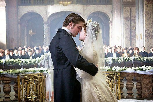 Bel Ami: Georges (Robert Pattinson) leans in to kiss Suzanne (Holliday Grainger) in front of their friends and family. Source: Magnolia Pictures