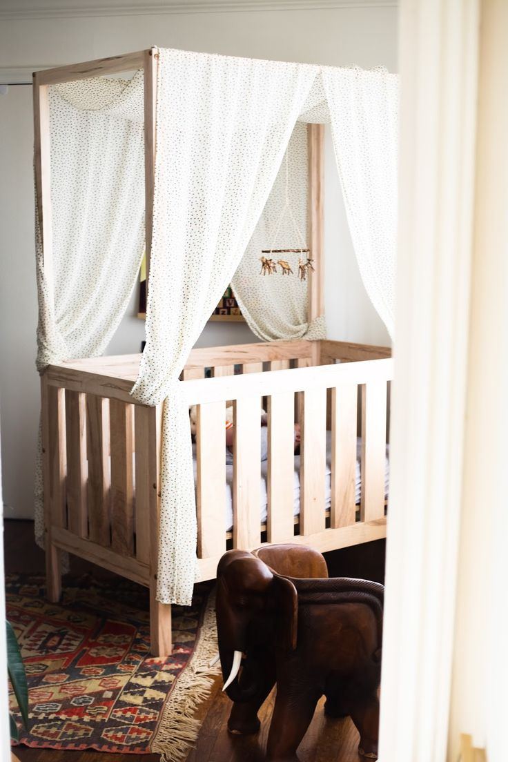 crib with a canopy to block sunlight during baby's naps in the nursery