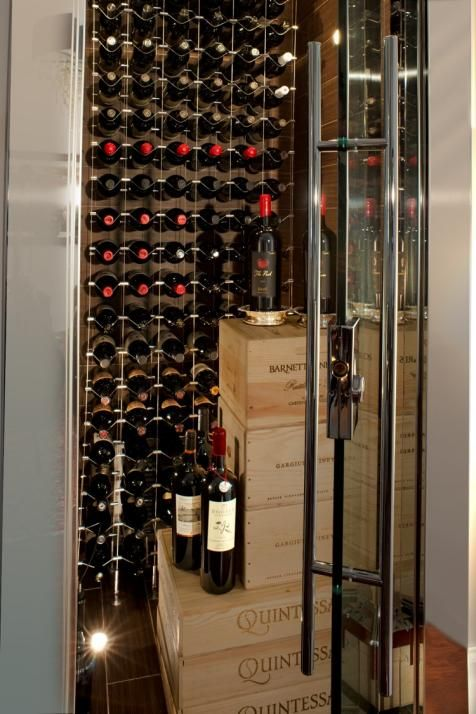 A small coat closet was torn out and revamped into this refrigerated wine cellar, complete with porcelain tiled surfaces that resemble wood texture and a chrome cable system that's suspended via bolts in the ceiling and floor. The 8-foot-tall entrance is outfitted with a commercial-grade glass door and chrome frame reminiscent of what's used for hotel elevators.