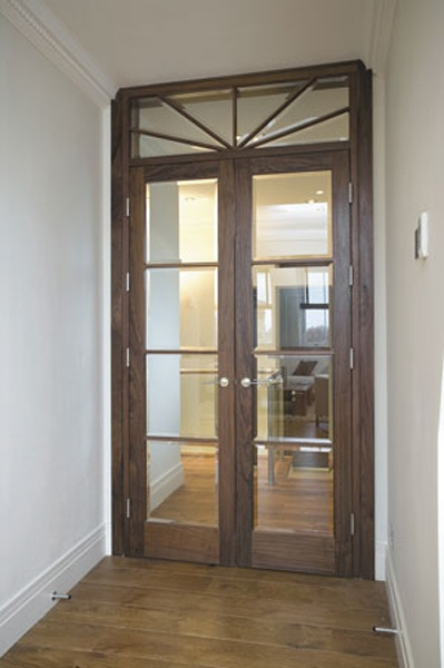 Walnut and glass door with fanlight which echoes the town house doors with fanlights so prevalent in Georgian and Regency London. This imposing door uses bevelled glass to create a beautiful effect as the refracted light filters in.