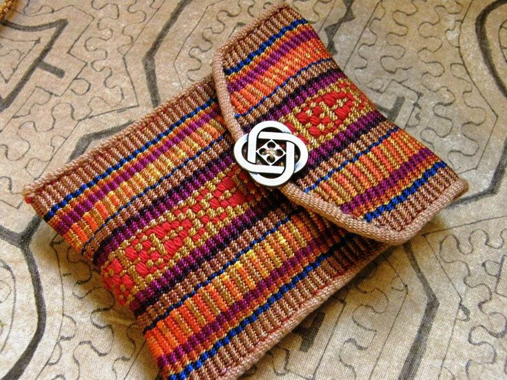 A friend gave me some reeled silk that she had hand painted and hand dyed. She put the colors together and let me weave it on my backstrap loom. I decorated the piece with tencel supplemental weft used motifs inspired by Andean textiles.Then, I cut it to make this small pouch. I applied a woven tubular band to the edges and around the shaped flap.