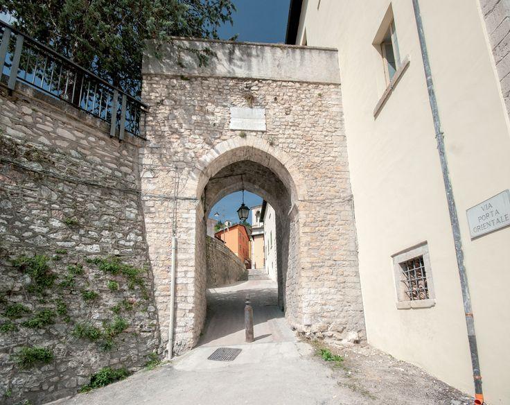 """Porta Orientale - Delle sette porte presenti nella cinta muraria, se ne conservano ancora due nella parte bassa della città: la Leonina e l'Orientale. Il Castrum Cassiae, sviluppatosi dal punto più alto verso il basso a semicerchio lungo il colle di Sant'Agostino, delimitato e difeso a nord dalla stretta gola del Corno e ed est dal fosso denominato di """"Cuccaro"""", era quasi inespugnabile."""
