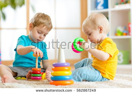 Children playing together. Toddler kid and baby play with blocks. Educational toys for preschool and kindergarten child. Little boys build pyramid toys at home or daycare.