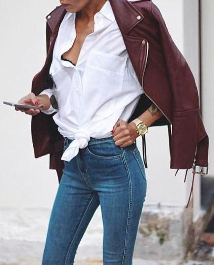 white tie shirt. blue skinny jeans. belted leather jacket.