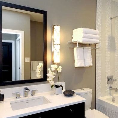 Contemporary Bathroom Design (Like the contrast of the white bath appliances with the wood mirror frame / cabinet brought together by the taupe bathroom paint.) The lights are also cute.