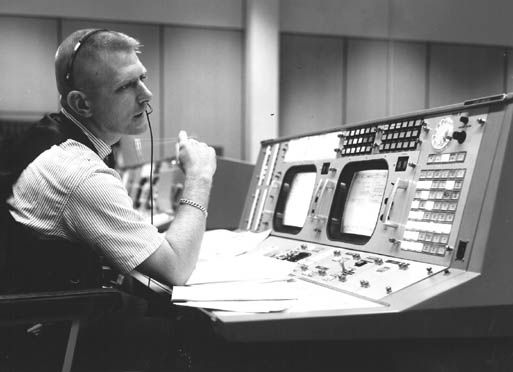 Eugene F. Kranz, flight director, is shown at his console on May 30, 1965, in the Mission Operations Control Room in the Mission Control Center at Houston during a Gemini-Titan IV simulation to prepare for the four-day, 62-orbit flight.