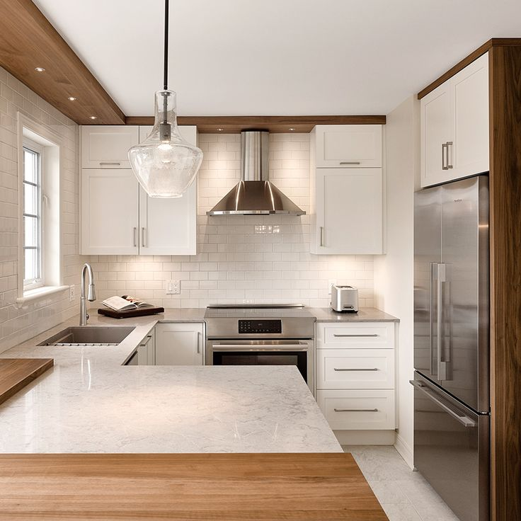 This compact transitional kitchen is beautifully composed with white cabinets, an undermount sink, granite countertops and white backsplash. Everything is enhanced by some gorgeous wood accents. By : Gagnon Cuisine