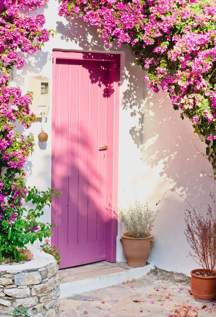 A nice greek house with a pink door and bougainvillea