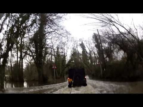 Surfing on the flooded roads, pulled along by a Land Rover.  Wakeboarders enjoying the recent floods in England.