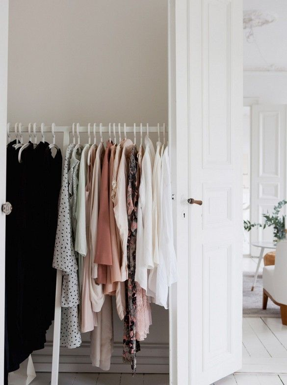 White clothes rack in white bedroom that is color coordinated