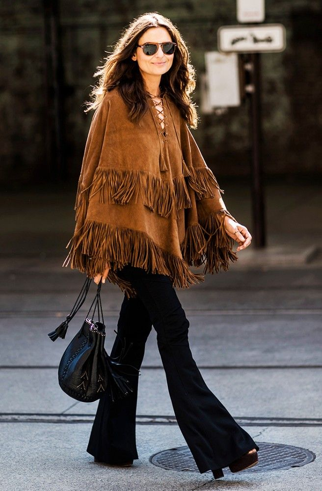 A suede fringe poncho is paired with flared jeans, platform sandals, and a bucket bag: