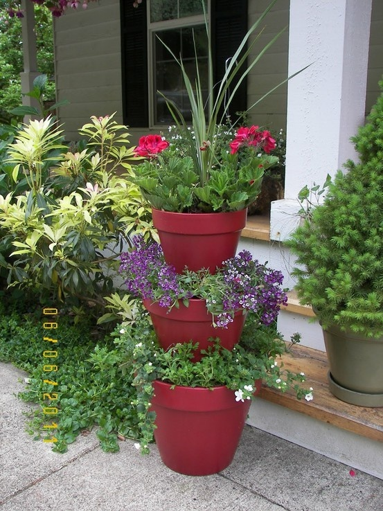 "She used 12, 10, and 8"" terracotta planters she painted, then used older TC planters inverted as stacker all on a dowel.  Cute front porch idea mandmplus3"