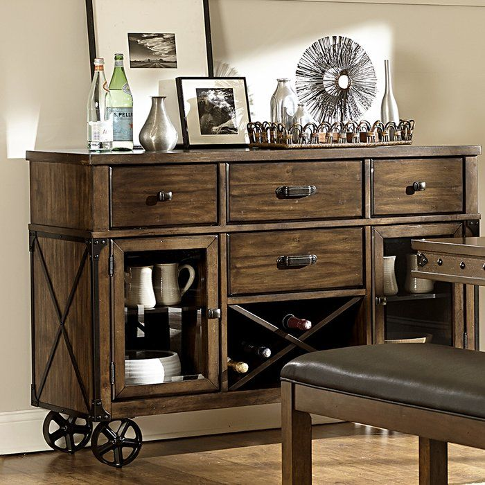 Transitional design combined with the trend forward look of industrial styling creates the look. Turnbuckle accents paired with faux rivets lend to the design of the table and accompanying sideboard. A burnished finish is utilized to highlight the wood grain veneer. The sideboard features drawer and door fronted storage along with wine rick and stationary leg supports that mimic industrial cart wheels.