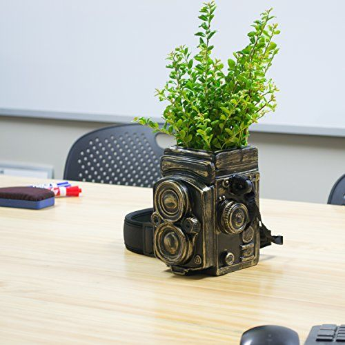 Vintage Camera Style Ceramic Decorative Vase.   --› A ceramic planter pot designed to look like a vintage camera.  --› The adjustable, removable strap looks just like a real camera strap, complete with padding.  --› Classic decoration for home or office.  --› No draining hole at the bottom.