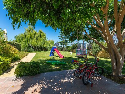 Rethymno villa rental - Lawn covered playground with children's toys.