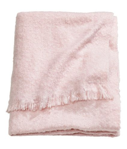 Light pink. Throw in soft woven fabric with fringe on short sides.