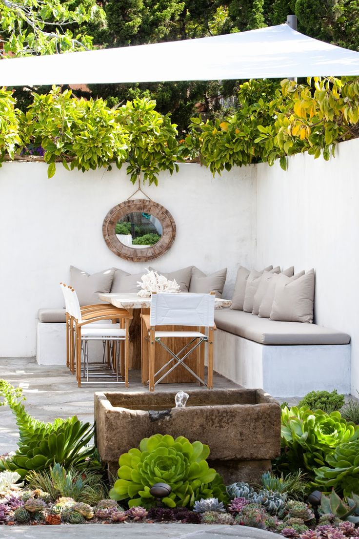 idées déco terrasse aménagée avec une voile d'ombrage blanche et décorée de succulentes et un miroir mural rond