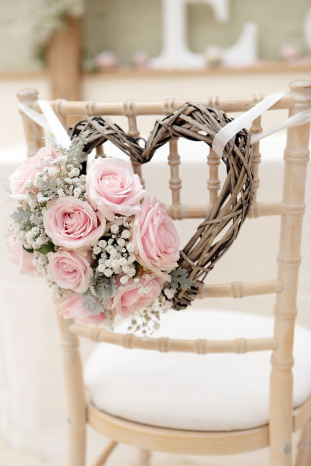Romantic rustic wedding decor: heart made from branches (ish) with classic pink hearts and baby's breathe.