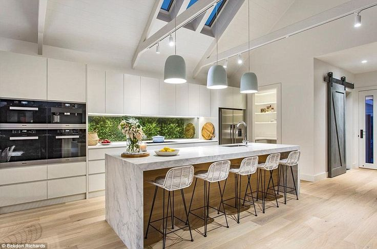 The kitchen features a massive Calacatta marble island bench lit by handmade ceramic penda...