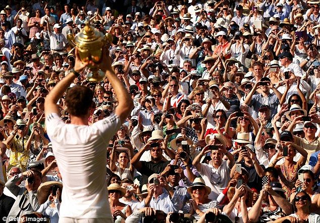 Murray lifts the famous trophy to the adoring Centre Court crowd after his win