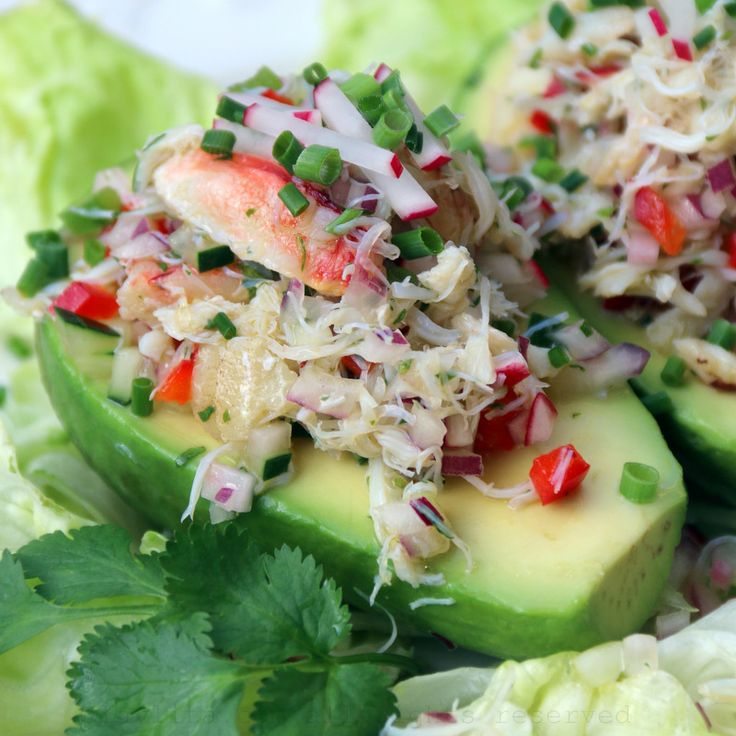 Recipe for crab salad stuffed avocados, prepared by filling avocados with a salad of crab, onion, bell pepper, cucumber, radishes, lime juice, olive oil, and cilantro.