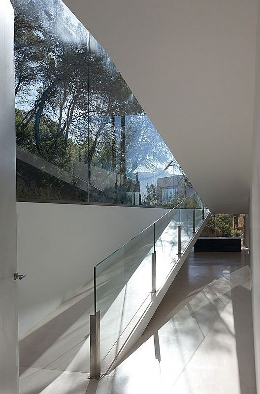 Minimalist House // using a ramp instead of stairs gives this house a very fluid feel. The glass, white interior finishes & simple steel handrail details are beautiful.