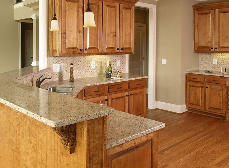 Giallo Ornamental Granite With Light Wood Cabinets.