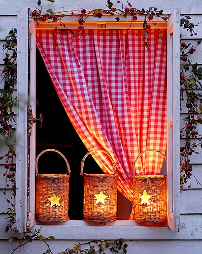 beautiful wicker storm lanterns with a lit candle in them. they have a sturdy glass liner, so they can be used as a vase too. I want these for my porch!