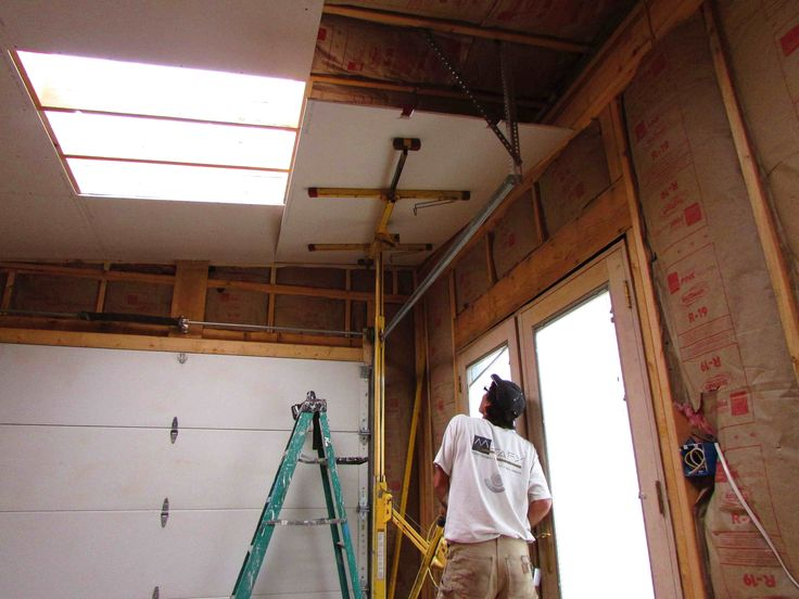 Jason Krause uses a drywall jack to attach sheets to the ceiling.
