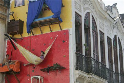 Brazil Art - Two brothers in Brazil are literally living on the outside of a building in Rio's Old Center and all in the name of art. Since May, twenty-seven-year-old Tiago Primo and his twenty-year-old brother Gabriel, have been sleeping, working and eating on the side of a building 33 feet (10 meters) up in the air for twelve hours every day.  They plan to continue this display until August 2009