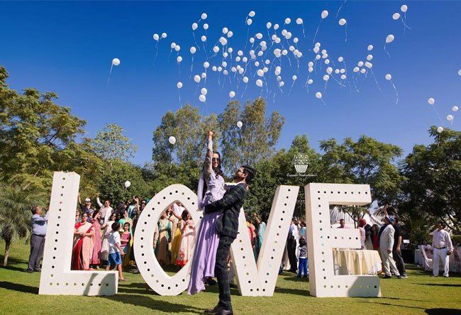Love alphabets with balloons in white with Indian couple posing | Indian wedding photo booth ideas | Photo Op ideas | fun wedding photos | Cupcake Production | The ultimate guide for the Indian Bride to plan her dream wedding. Witty Vows shares things no one tells brides, covers real weddings, ideas, inspirations, design trends and the right vendors, candid photographers etc.| #bridsmaids #inspiration #IndianWedding | Curated by #WittyVows - Things no one tells Brides | www.wittyvows.com