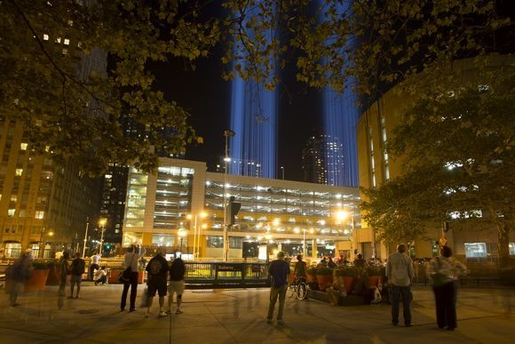 People congregate in a small park between Greenwch St and Trinity Pl in lower Manhattan on September 11, 2014 to observe the Tribute In Light that eminates from the top of the Battery Parking Garage located several blocks south of the WTC site.Photo By: Robert Breese/For the Times Herald-Record