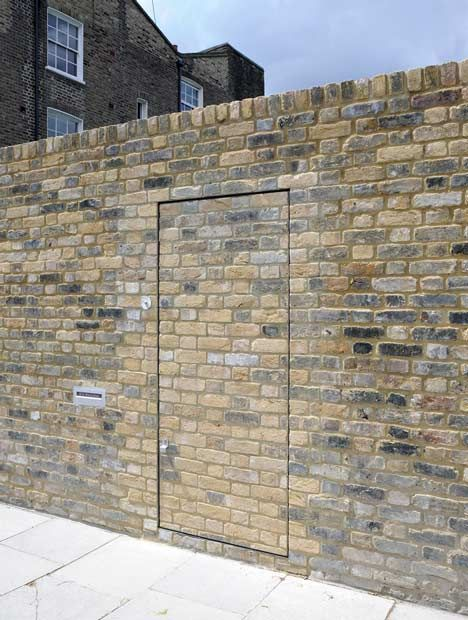 People strolling by this brick wall in London might miss the disguised entrance to a secret office and home.