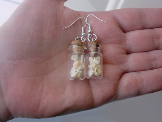 Simple but beautiful bones. These earrings feature rat bones from an owl pellet. I am 100% certain on them being rat because the pellets were from raptors at a rehabilitation facility that were fed on a diet of rats and quail (and these bones definitely aren't quail). Inside each glass vial are small rat bones such as ribs, scapula, femurs, radius and jaw bones. Both vials also contain a few molars and an incisor.  SOLD.