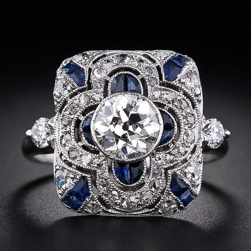 This is an exquisite dinner ring from the early 20th century. This early Art Deco ring centers an .80 carat European cut diamond bezel set in a rectangular plaque which is delicately pierced and set with both glittering antique cut diamonds as well as calibre cut synthetic sapphires. A round cut diamond highlights each shoulder.