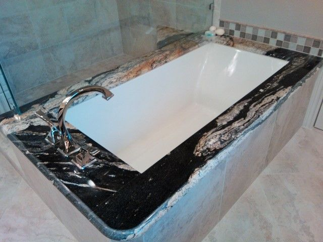 Gorgeous black, cream, and tan swirled granite bathtub. (By John Voigt Designs)