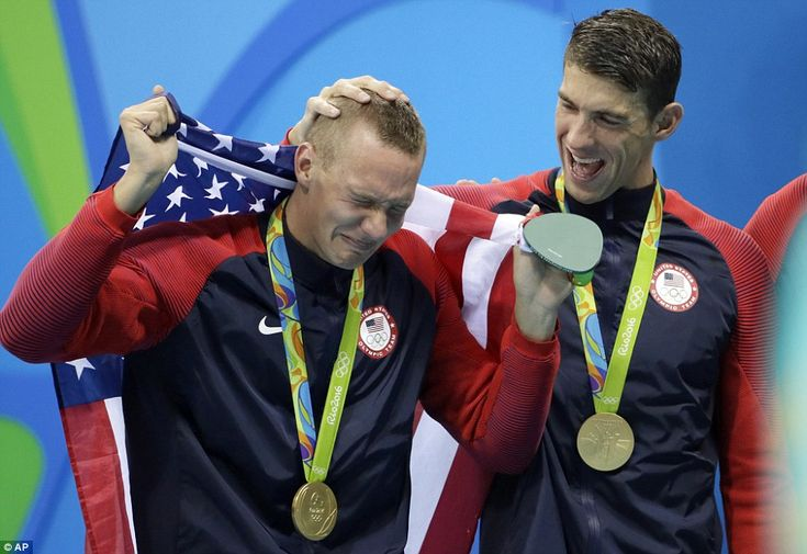 Caeleb Dressel (left) cries as he walks with an American flag, while Michael Phelps celebr...
