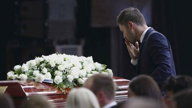 The saddest day in cricket... Michael Clarke pauses at his friend Phillip Hughes' casket as he makes his way to the lectern to deliver his tribute.