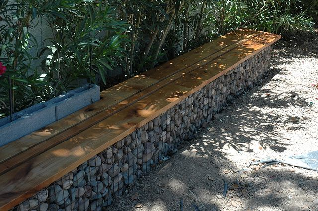 gabion benches gabion cages topped with wood seat.. Gabion cages carried around tree along fence to provide bench for seating