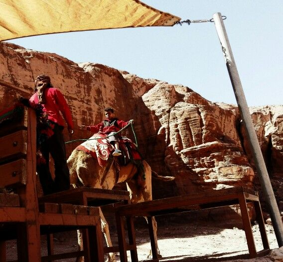 Seven years old boy riding a camel..