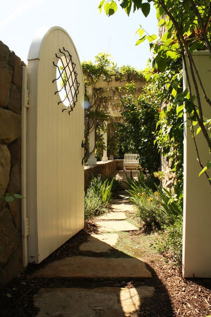 Lovely gated entry to pergola covered rock wall veranda