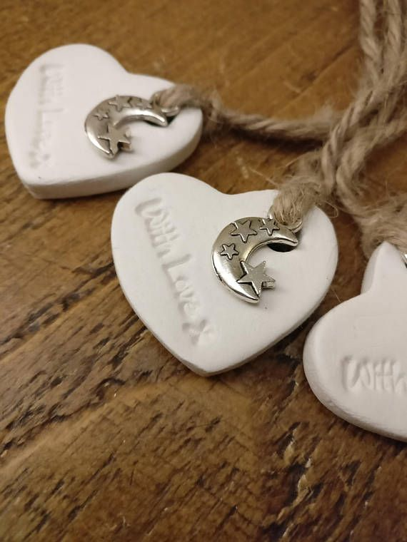 5 white clay heart tags A set of 5 white clay hand crafted heart tags, hand stamped with -with love- and decorated with a silver moon and stars charm. A perfect finishing touch to gifts or wedding favours. Each tag is made individually by hand making each one entirely unique and one