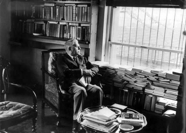 """Montale tra i suoi libri a Milano. A dispetto dell'ego di molti autori contemporanei, scriveva di sé nelle quarte di copertina delle sue opere: """"Eugenio Montale è nato a Genova il 12 ottobre 1906 e vive a Milano. Dottore in lettere, giornalista, scrittore, poeta, premio Nobel per la letteratura nel 1975""""."""