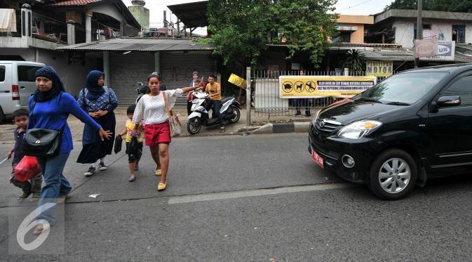 Pejalan kaki menyeberang meski terdapat tulisan agar tidak menyeberang sembarangan di jalan raya Lenteng Agung, Jakarta (3/12). Ironisnya, tak jauh dari lokasi terdapat Jembatan Penyeberangan Orang (JPO) yang masih berfungsi. (Liputan6.com/Yoppy Renato)