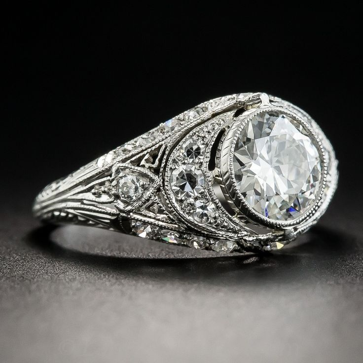 Few original Art Deco engagement rings come as fine and fabulous as this intriguing jewel starring a beautiful bright European-cut diamond weighing 1.07 carats, accompanied by a GIA Diamond Grading Report stating: H color - VS2 clarity. The gorgeous stone sparkles intensely from within a delicately milgrained bezel setting embellished on all sides by small glittering round diamonds, including a prominent pair of diamond-set crescents. Geometric piercing, fine milgraining and hand-engraved…