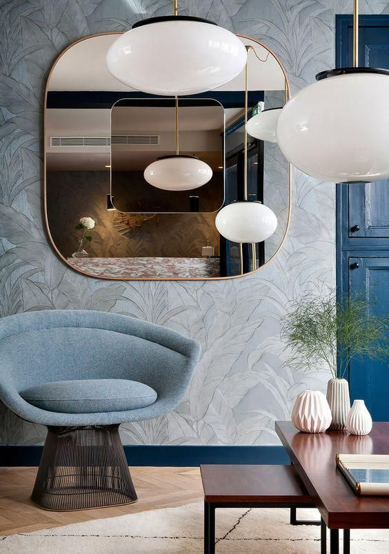 Gorgeous mix of shades of blue in contemporary and modern architecturally-inspired interior design styles in this Parisian hotel living room vignette with mod bubble pendant lights, a glam pedestal accent chair and a low glossy wood midcentury bench.