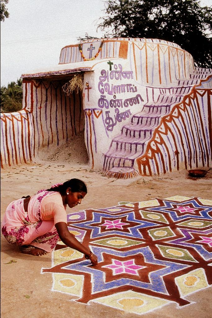 """""""A woman painting a kolam in Tamil Nadu, India.A kolam is a form of sandpainting that is drawn using ricepowder by female members of the family in front of their home."""""""