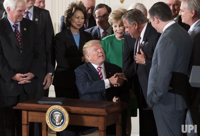 President Donald Trump shakes hands with Rep. Bill Shuster, R-PA, after he signed a letter of initiative to privatize the nation's air…